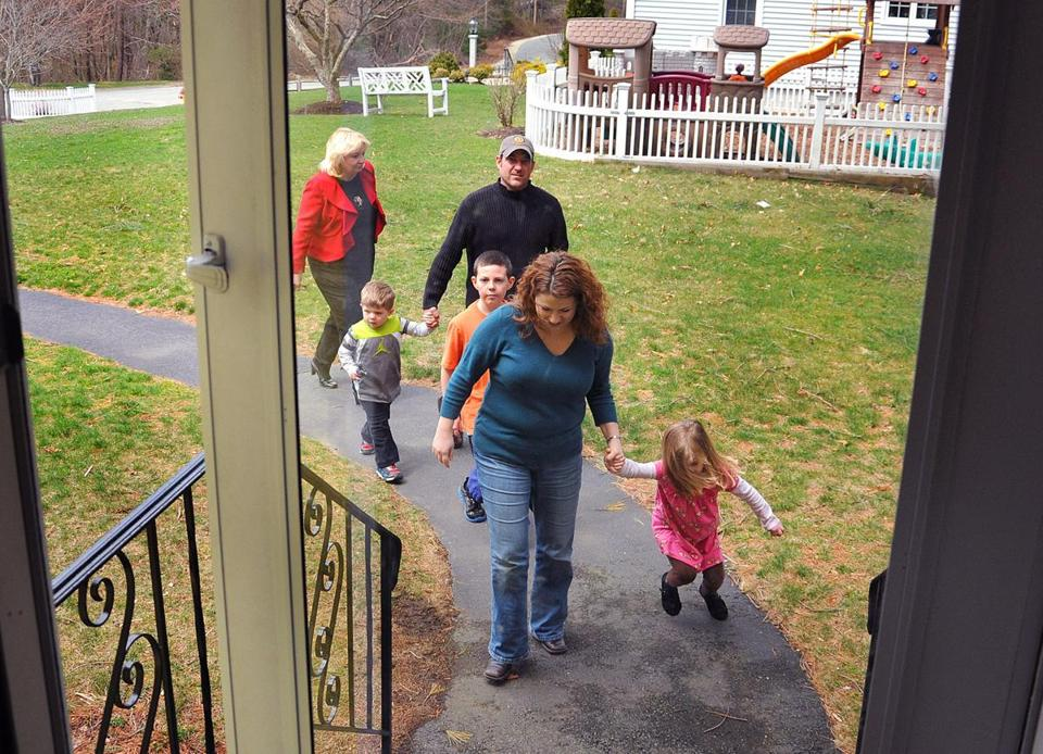 Katie and Jason Casavant and their children look at a house in Hanson with broker MaryBeth Muldowney.