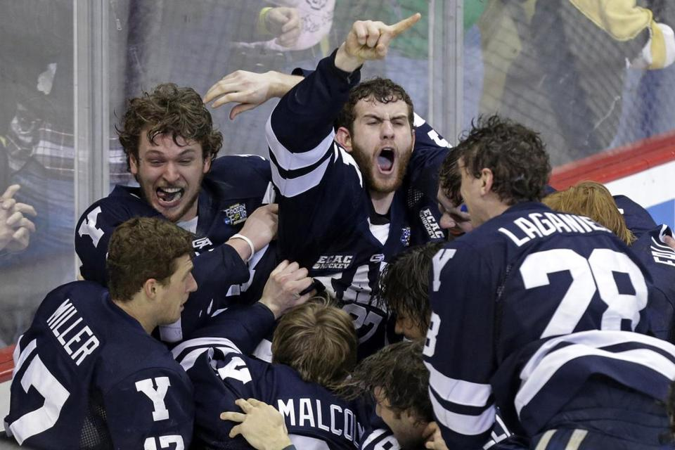 Yale goalie Jeff Malcolm was swarmed by teammates after shutting out Quinnipiac 4-0 to win the NCAA men's college hockey national championship.