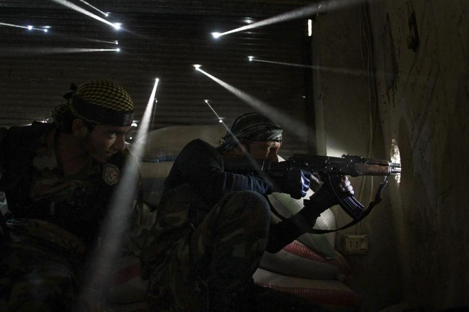 The Pulitzer Prize for feature photography honored Javier Manzano's image of two Syrian rebel soldiers guarding their position as light streams through bullet holes.