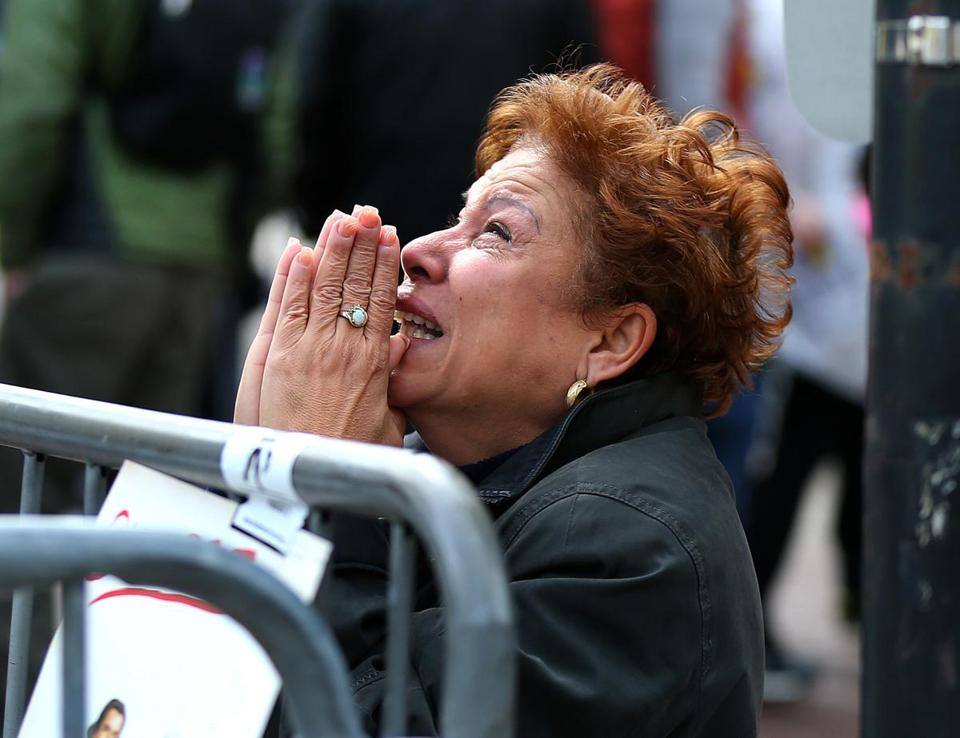A woman knelt and prayed at the scene of the first explosion at the Marathon finish line on Boylston Street.