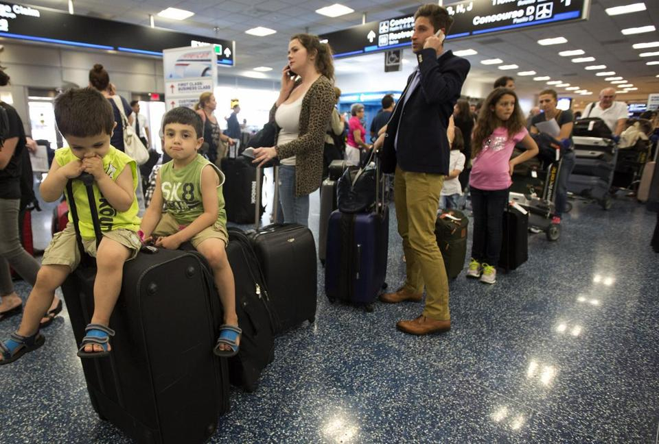 Yousef and Mohammed Saadah from North Carolina waited on top of the family luggage on Tuesday in the Miami International Airport.