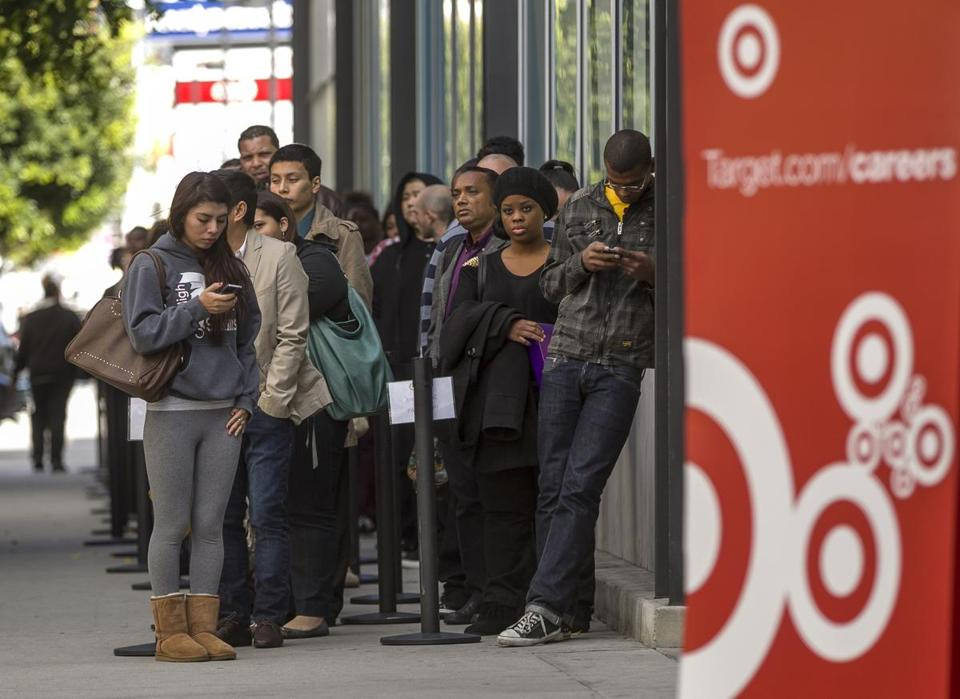 Job candidates waited outside a Target in Los Angeles in January. The retailer lowered its profit forecast.
