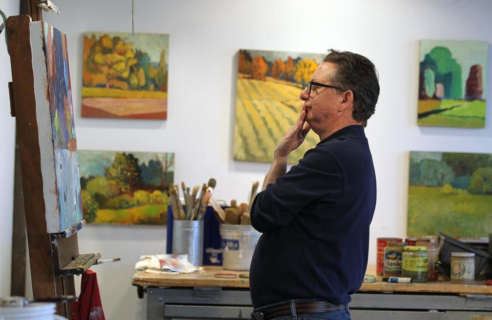 Matt Carrano examines one of his works at his studio in Somerville.