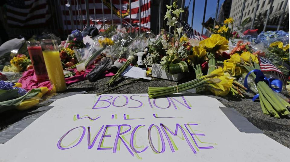 Flowers and signs adorn a barrier at Boylston Street near the finish line.
