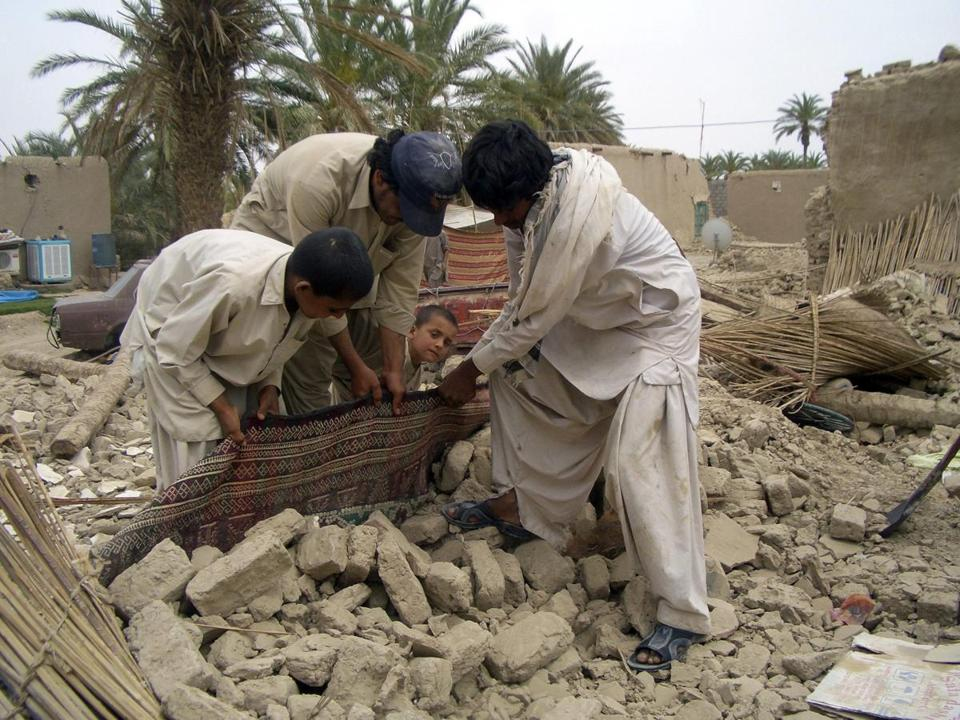 Survivors tried to remove a carpet from their home in Baluchistan Province in Pakistan. Thousands were left homeless.