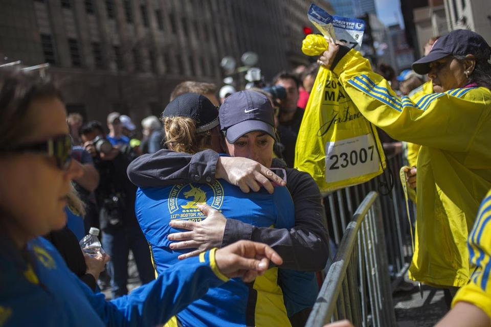 Runners hugged after picking up their effects at the finish line Tuesday.
