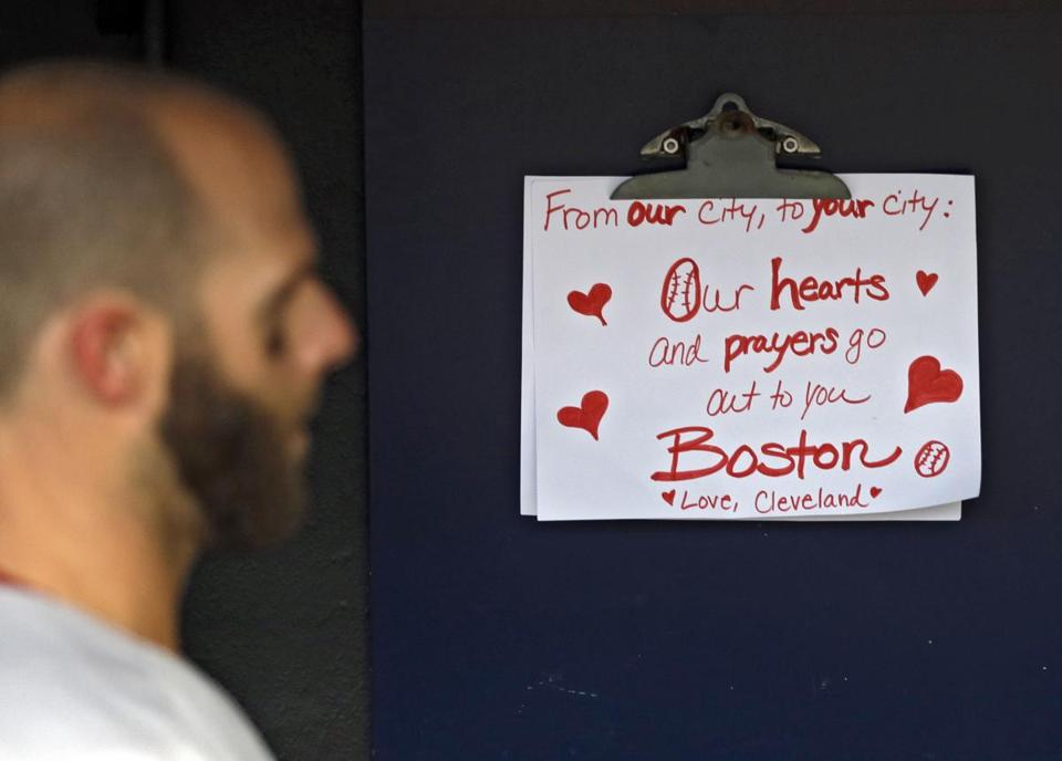 The Sox' Dustin Pedroia reads a sign of condolence from a Cleveland resident.