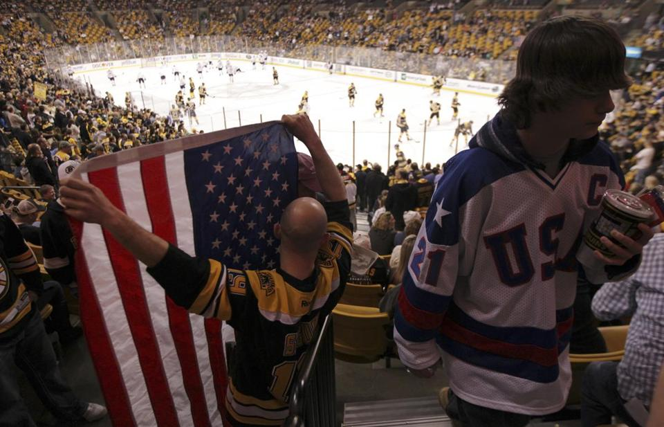 Paul Constantine, of New Bedford, holds up a giant American flag before the Bruins-Sabres game.