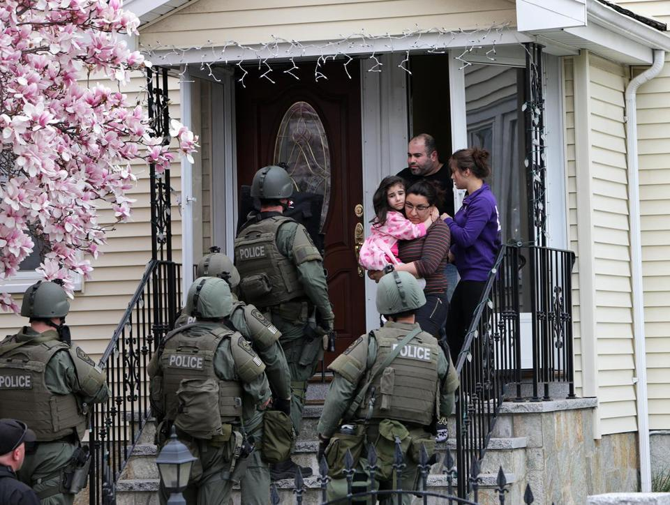 A SWAT team conducted a house-to-house search Friday in Watertown. Hundreds of police officers from across the region joined in such searches.