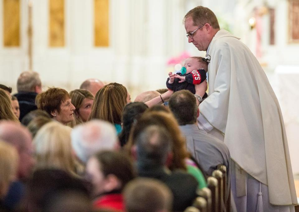 Father Sean Connor held a parishioner's child during his sermon at a mass at Saint Ann Parish Neponset in Dorchester.