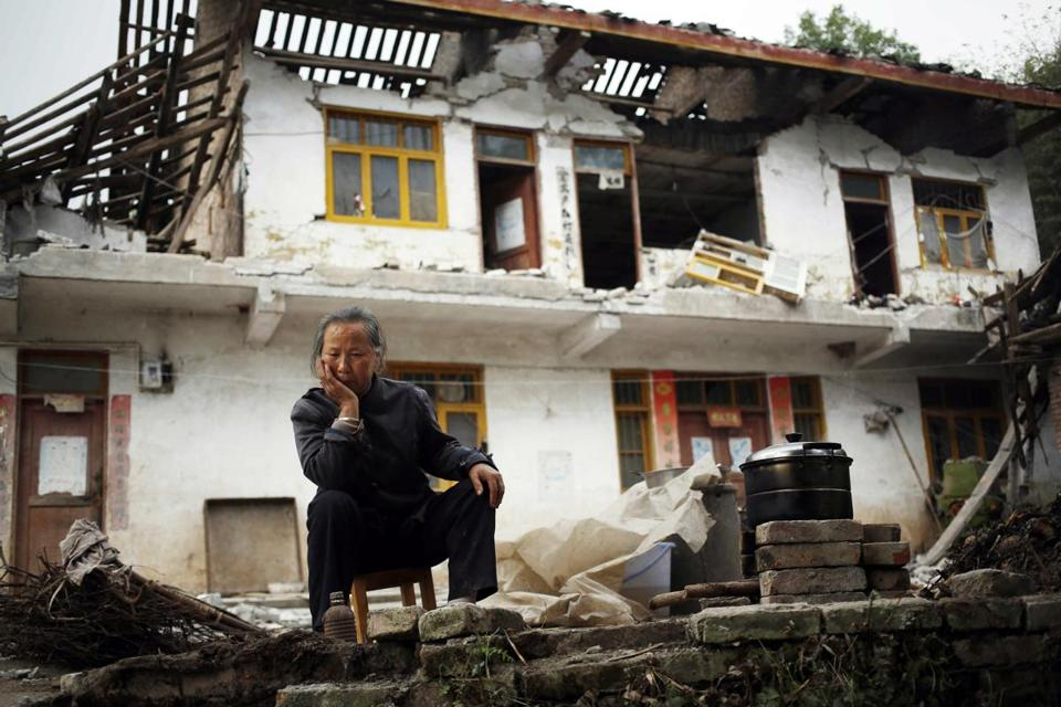 A resident of Ya'an, Sichuan Province, China, sat outside her home, which was damaged by an earthquake Saturday.