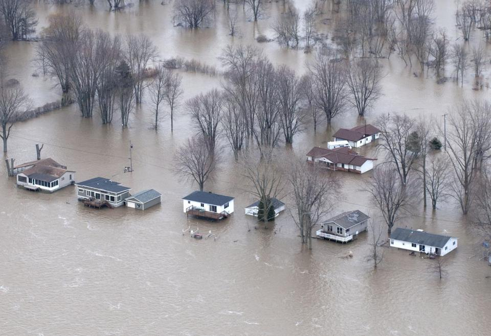 Homes in Robinson Township, Mich., were surrounded by Grand River flood waters Saturday. Weather forecasts are calling for more heavy rain in much of the Midwest.