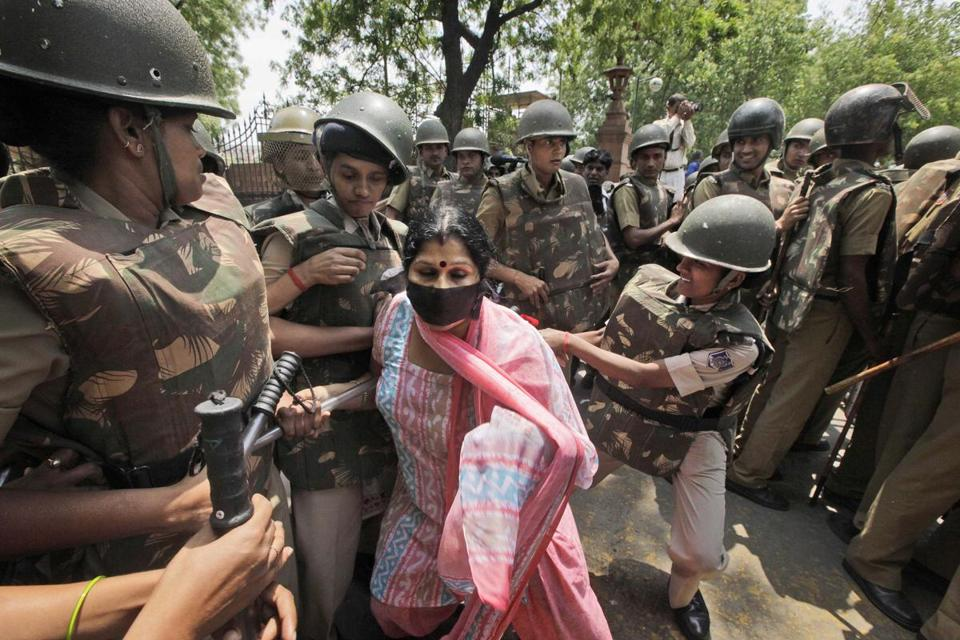 Female police officers detained a protester outside Parliament in New Delhi on Monday. Demonstrators have demanded that the Delhi police chief be removed from office.