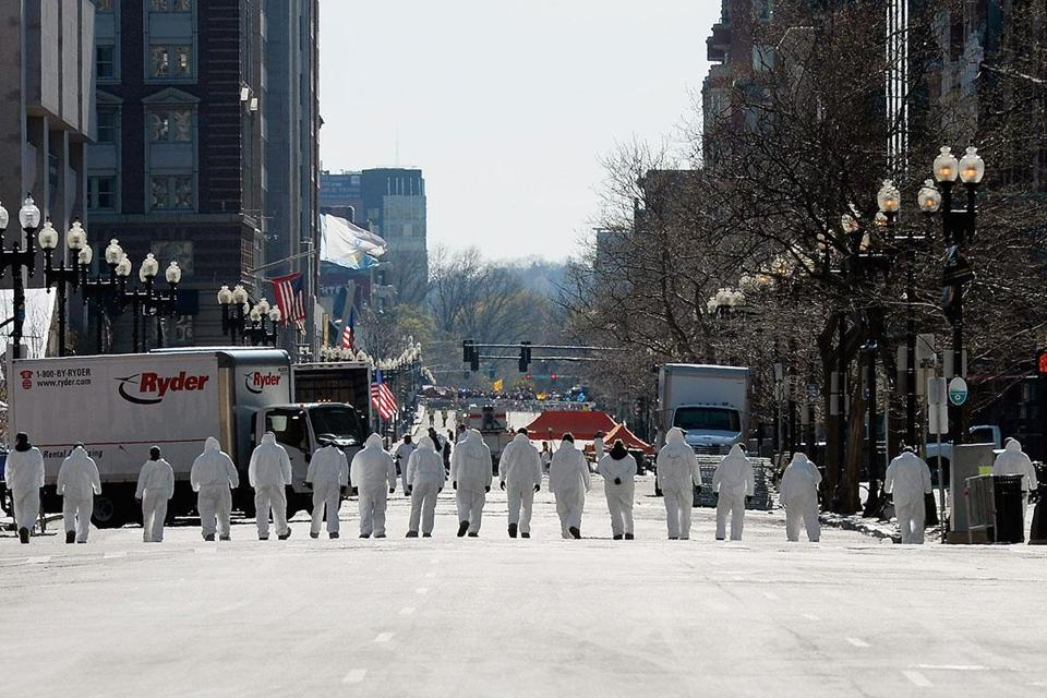 Looking for evidence in last Monday's bombings, law enforcement investigators walked the route of the Boston Marathon on Boylston Street Sunday.