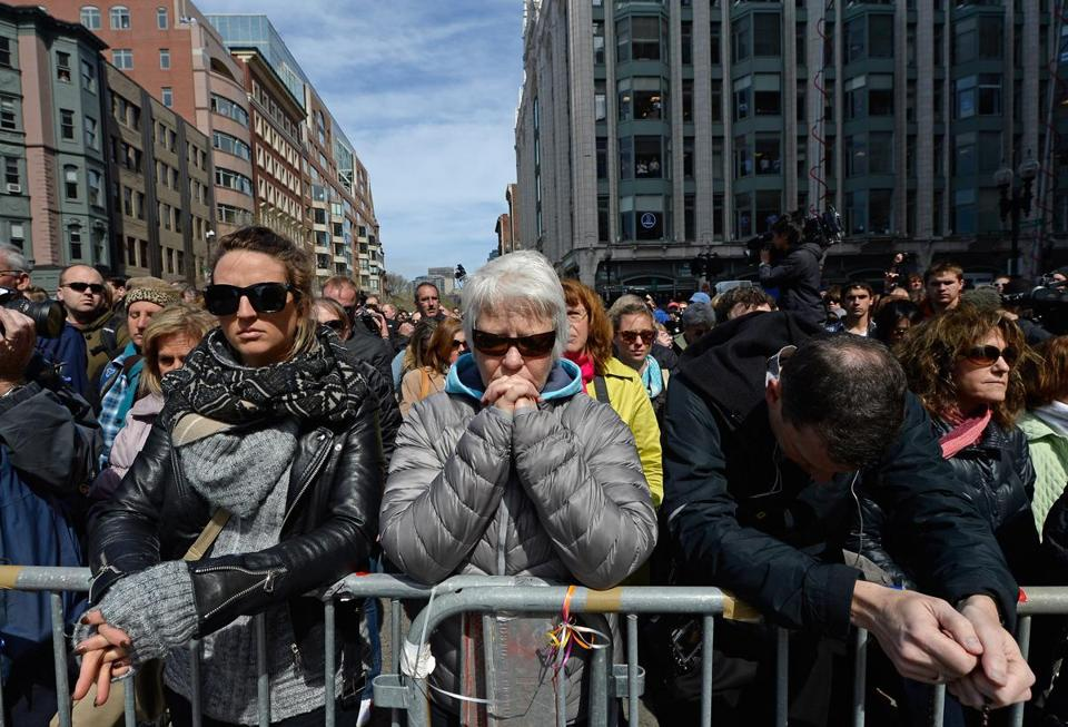 People observe a moment of silence near the Marathon finish line Monday.