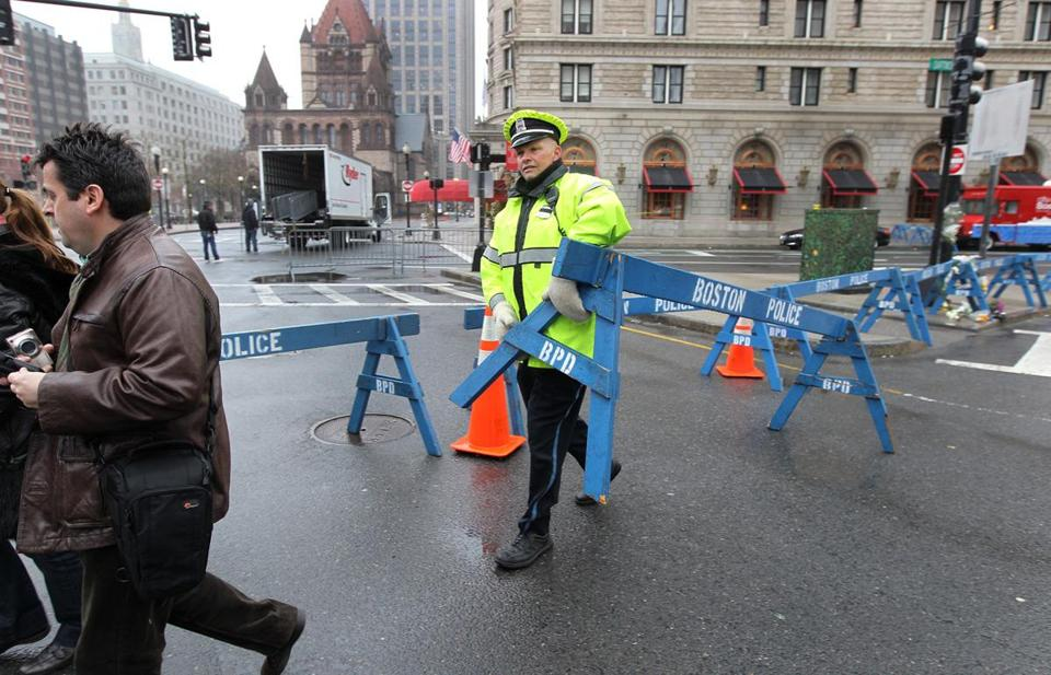 Boston Police Officer Mike Duggan repositioned a barrier as the city conducted a cleanup of Boylston Street on Tuesday.
