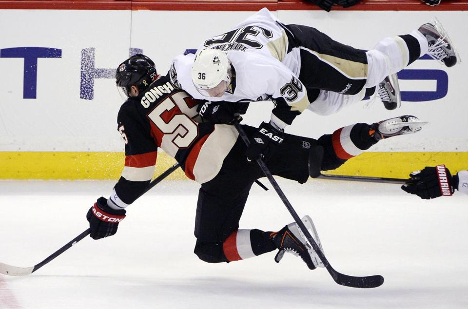 Flying Penguin Jussi Jokinen delivers a shot on Ottawa's Sergei Gonchar.