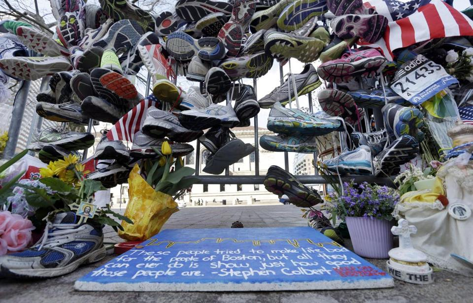 Running shoes hung on a fence Thursday at a makeshift memorial near the Marathon finish line.