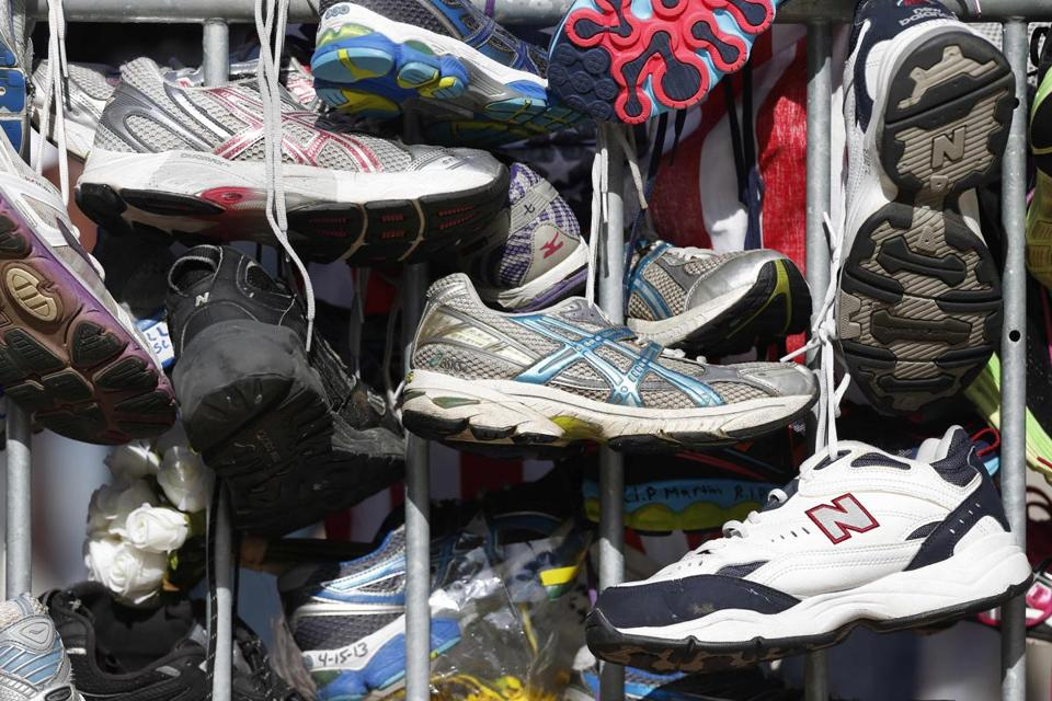 Running shoes hung from a barrier at a makeshift memorial in Copley Square on Boylston Street.