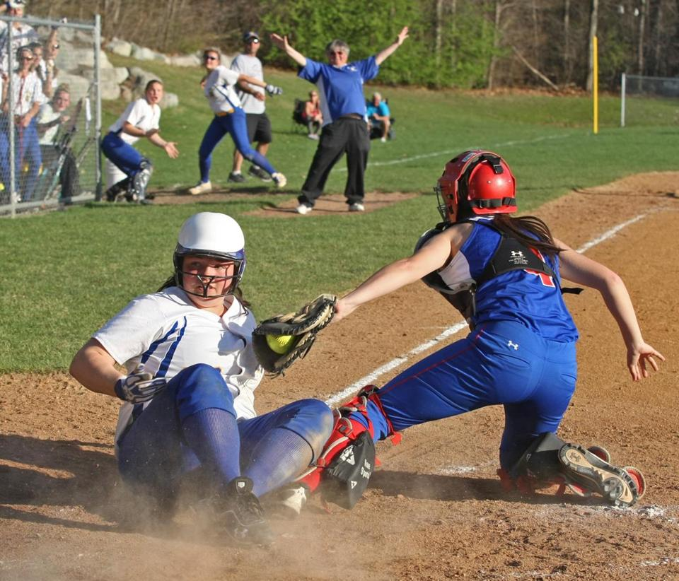 Norwood's Kelly Duggan slides across home plate past the sweep tag of Natick catcher Lauren Crowley in the bottom of the 7th inning Wednesday to tie the score at 5-5, which has coach Carol Savino celebrating. At left, Makenna Lane (far left) and first baseman Jess Gorman (right) join pitcher Jill Shepherd for a mound conference after she was touched up for three runs in the first inning. Natick scored four runs in the 9th inning to win 9-5 on the road.