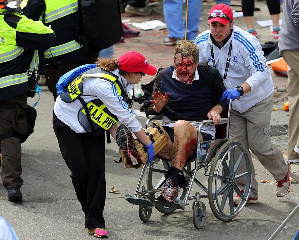 Medical workers aid an injured man at the Marathon after two bombs exploded near the finish line. David L. Ryan Photo/Boston Globe.