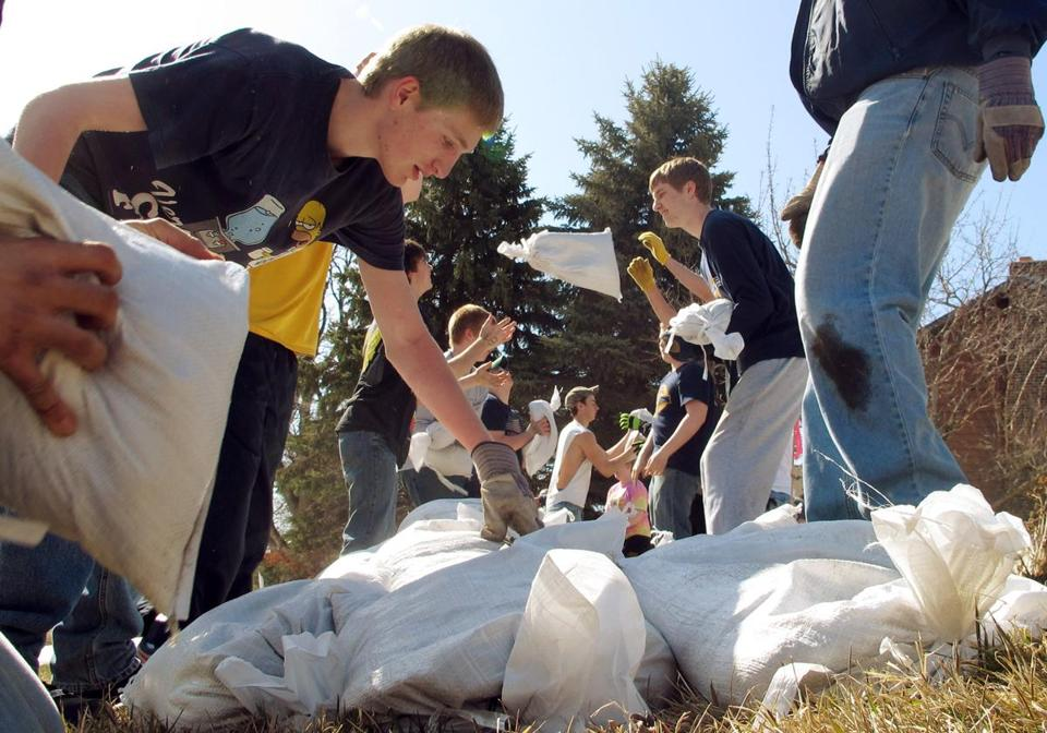 Hundreds of students pitched in Friday to place 100,000 sandbags around Fargo as the Red River rises.