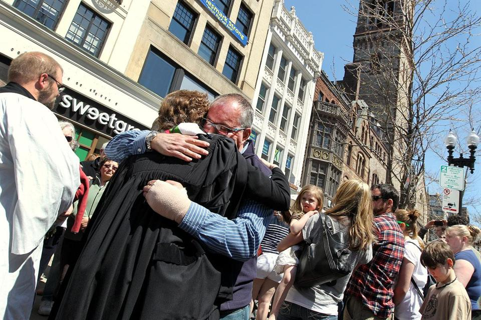 Tom Ralston, 54, of Revere, hugged Nancy Taylor, Old South Church's senior minister, as the church's Great Tower Bell tolled Sunday for those killed during the week of the Marathon bombings.