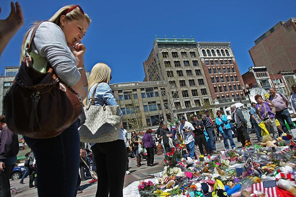 Brianna Flynn (left) stopped to reflect at the ever-expanding Marthon memorial at Copley Square.