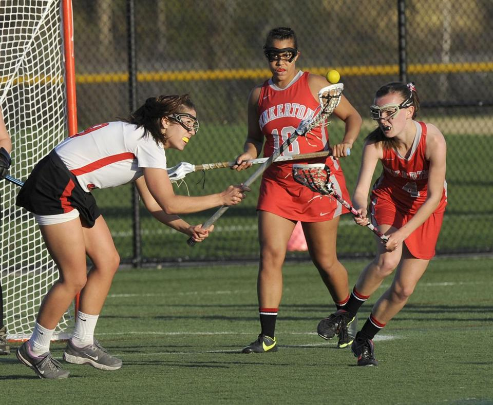 North Andover's Audrey Samuelman (left) battles Pinkerton Academy defenders Tuesday. Samuelman is one of three senior captains for the Scarlet Knight girls' lacrosse squad.
