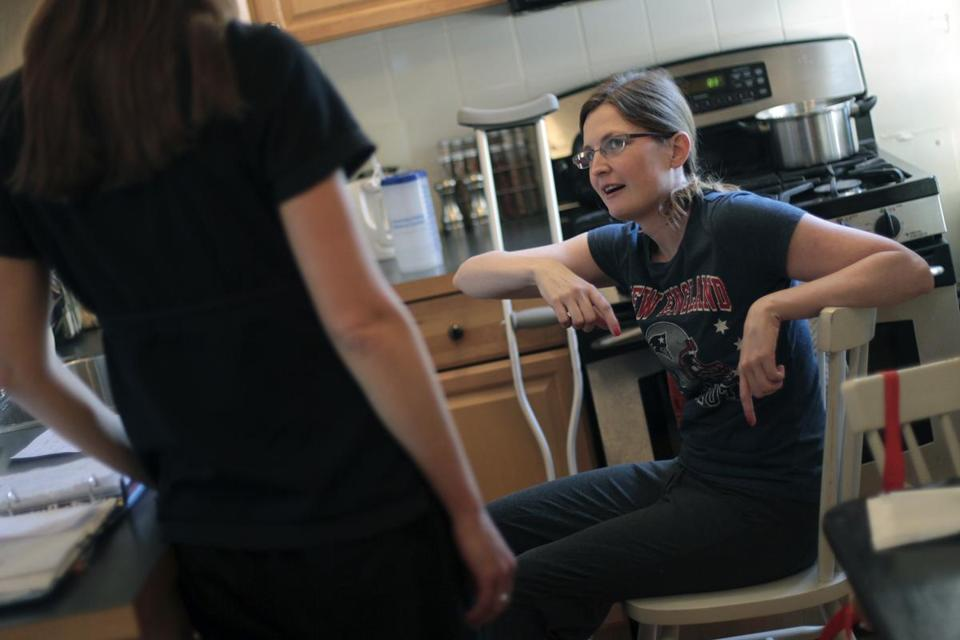 Therapist Erin Saulnier worked with Brittany Loring (right) earlier this month in her Cambridge apartment.