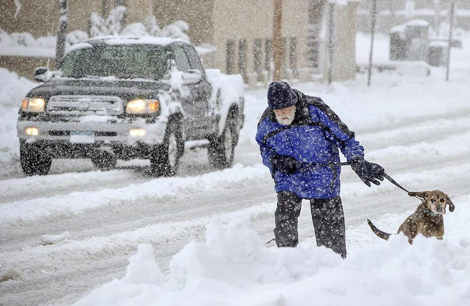 Mike Gregg and his dog trudged through snow for a walk in Austin, Minn., on Thursday.