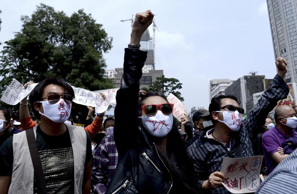 "Protesters in Kunming, in China's Yunnan Province, demonstrated against a planned refinery Saturday, wearing masks with ""No to Kunming PX"" written on them."