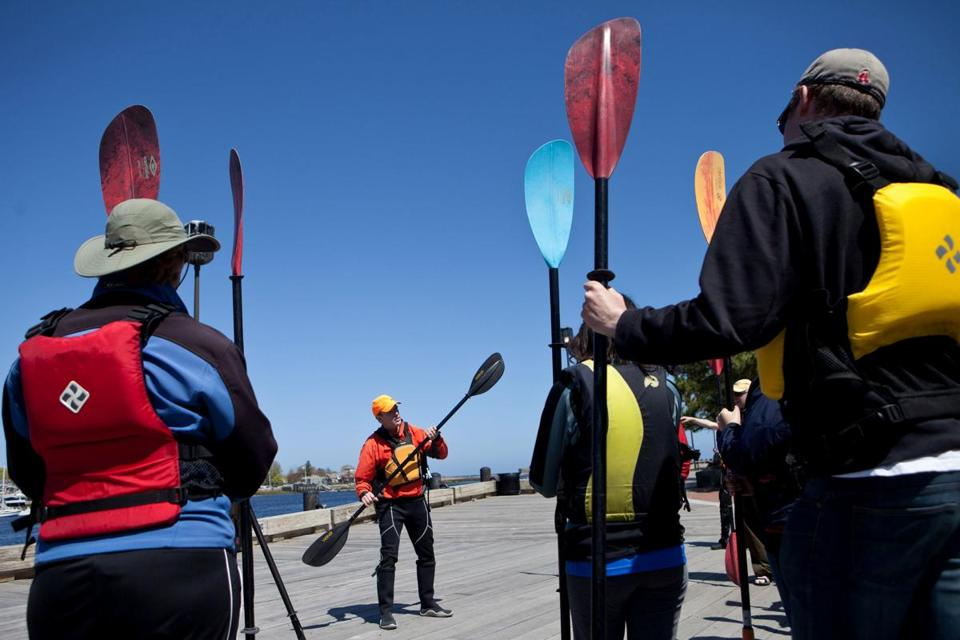 Plum Island Kayak owner Ken Taylor (center) demonstrates the use of a paddle before a group of kayakers sets off on one of the Newburyport company's guided tours.