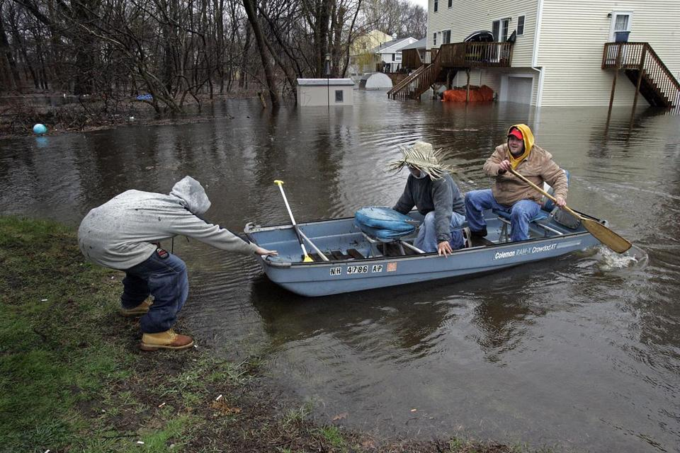 During April 2007 flooding in Lowell, residents move a boat to dry ground across a flooded yard on New York Avenue.