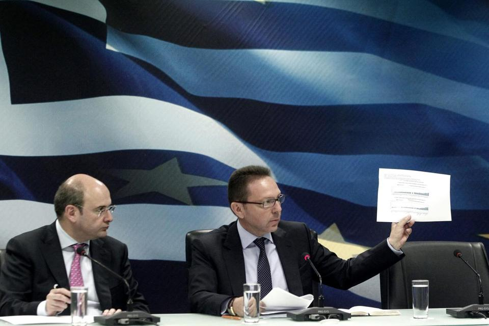Yannis Stournaras (right), Greece's finance minister, says the country is on track to ask for further debt relief.