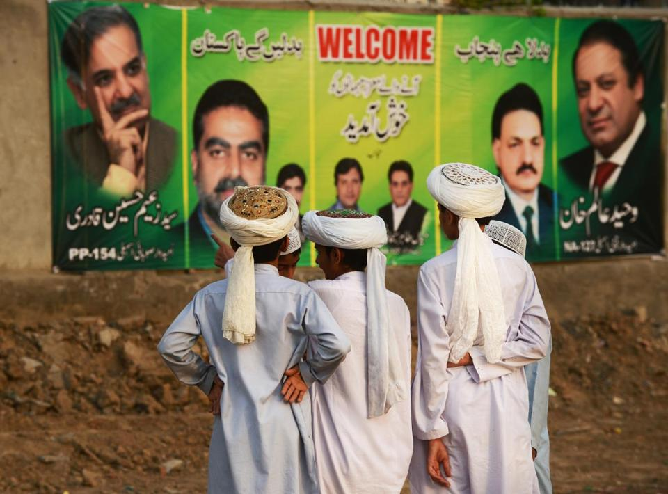 Supporters of Pakistan's Muslim League Nawaz stood near political posters during a rally in Lahore on Thursday.
