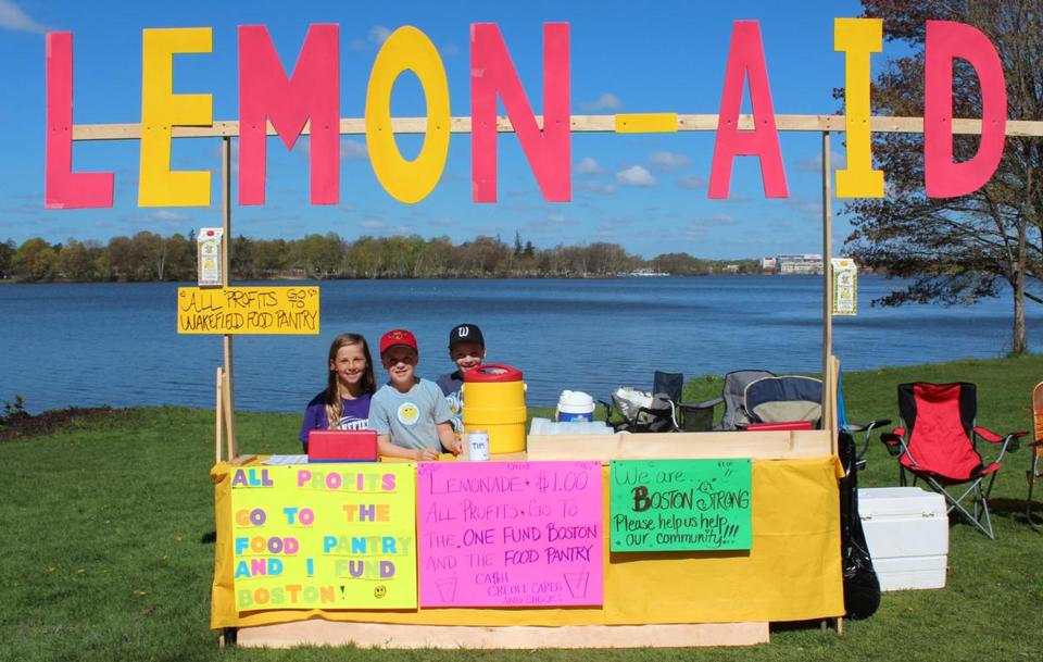 AID STATION — Wakefield students (from left) Summer Milsky, 8, Luke Greif, 6, and Noah Greif, 10, raised more than $1,300 on a recent Saturday with their Lemon-Aid 3 stand to benefit the One Fund Boston and Wakefield Interfaith Food Pantry.