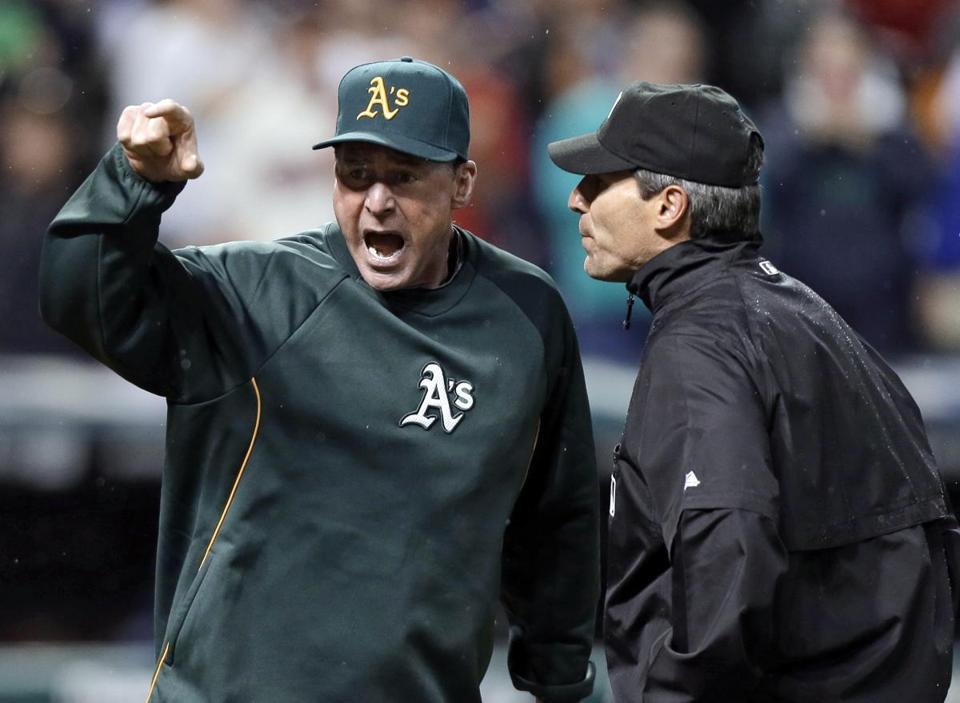 Oakland Athletics manager Bob Melvin, left, argued with umpire Angel Hernandez after a review failed to turn a double by Adam Rosales into a home run in the ninth inning. The Indians won 4-3.