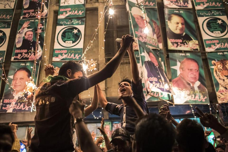 Supporters of the Pakistan Muslim League-N Party celebrate election results tabulated Saturday in Lahore.