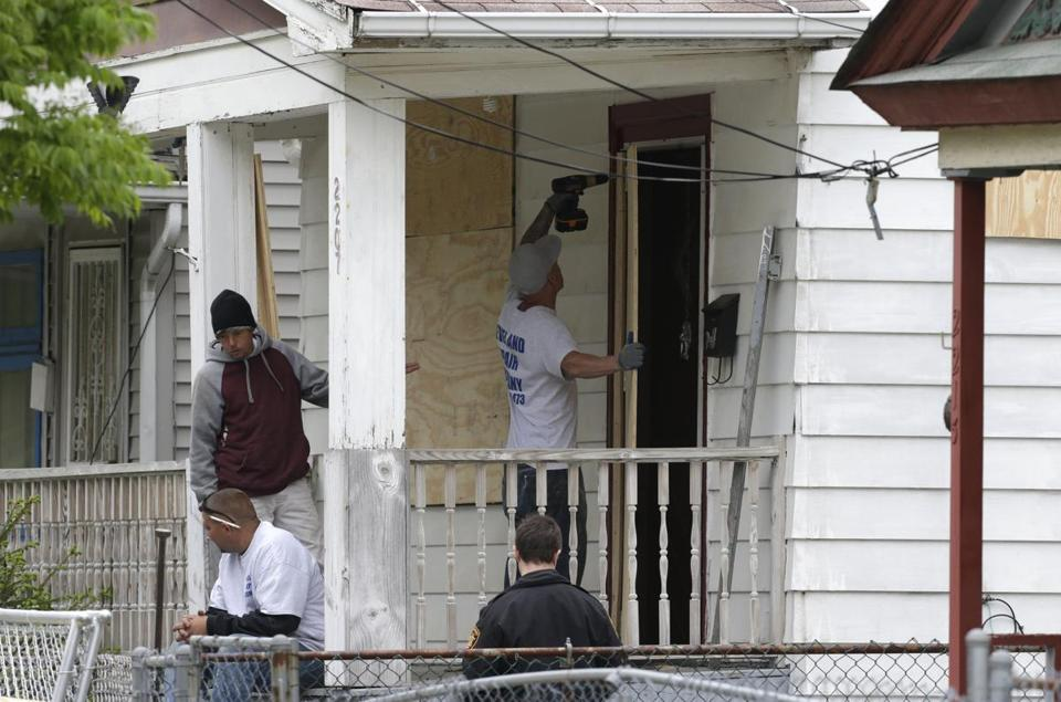 Workers boarded up the house where three women were allegedly held in Cleveland.