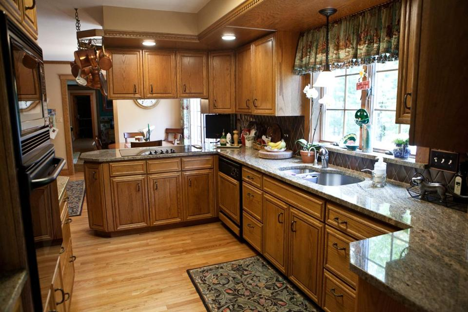 The Wholly Updated Kitchen Has Light Brown Granite Counters And Oak  Cabinets As Well As A