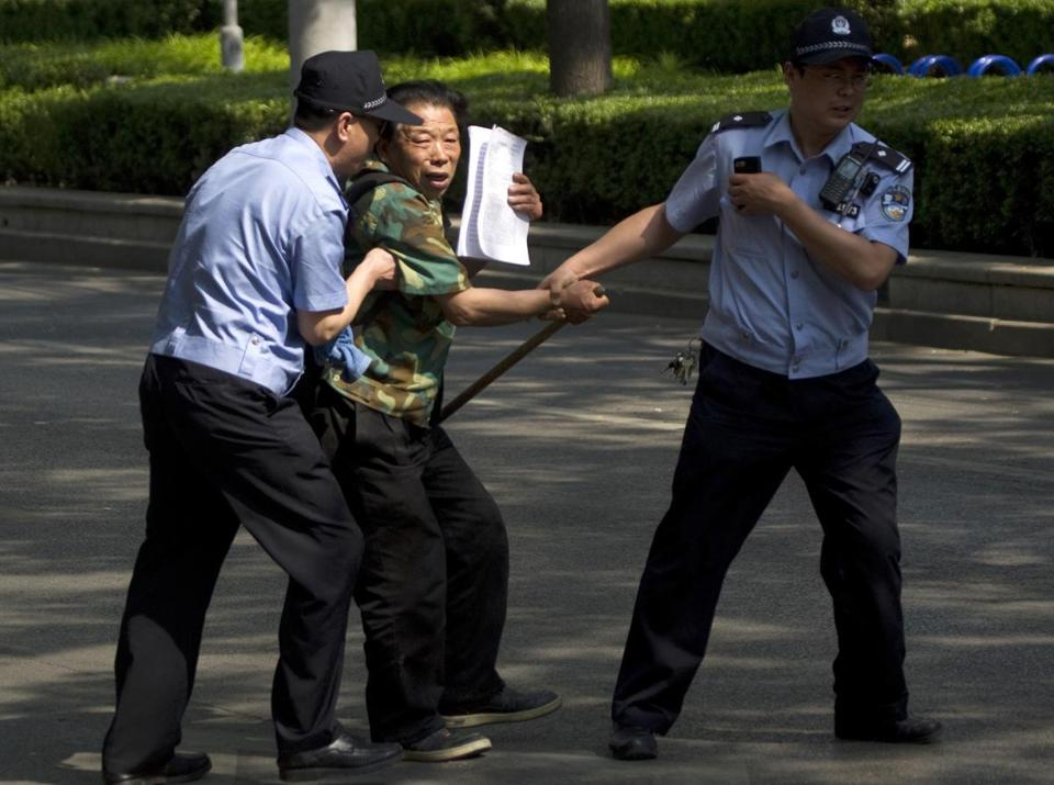A protester was taken away by police outside a Beijing hospital where activist Chen Guangcheng is being kept.
