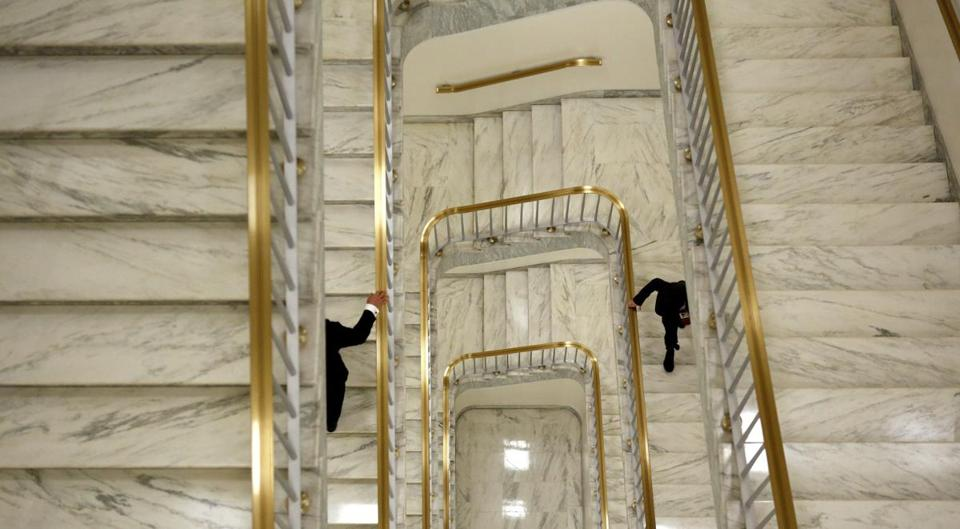 Two men held onto the bannister as they ascended a staircase in the Rayburn House Office Building on Capitol Hill.