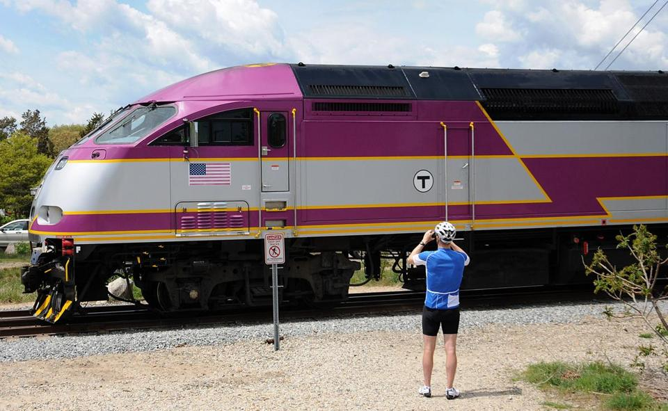 A bicyclist stopped to take a picture of the CapeFlyer train after it crossed over the Cape Cod Canal Railroad Bridge in Bourne.