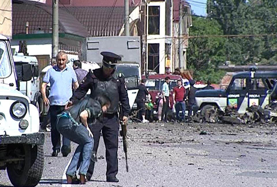 A video image showed a police officer helping a woman near a blast site in Makhachkala on Monday.