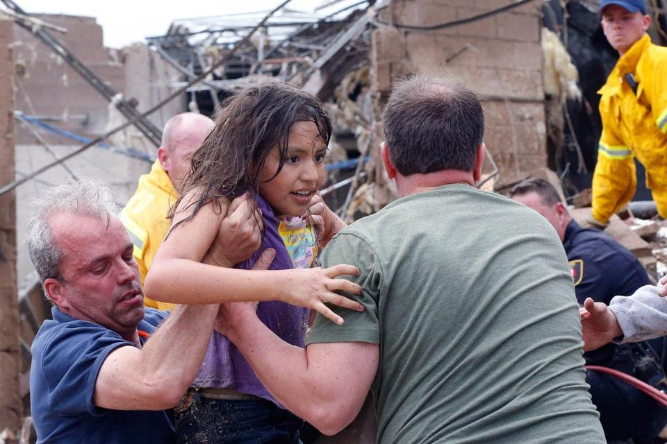 Rescuers pulled a child from the rubble of an elementary school in Moore, Okla., Monday and passed her to a triage center after a massive tornado tore through the Oklahoma City suburbs.