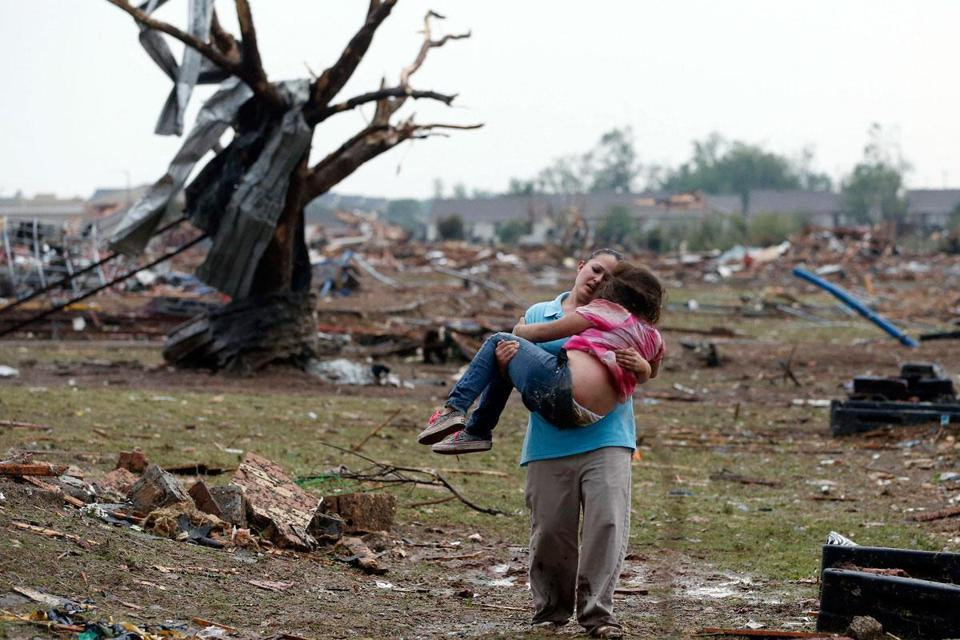 Near the collapsed Plaza Towers Elementary School in Moore, Okla., a child is carried from the devastation Monday.