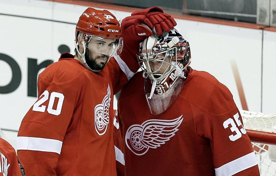 Drew Miller congratulates Jimmy Howard for making 39 saves — 16 in the third period — in Detroit's 3-1 victory.