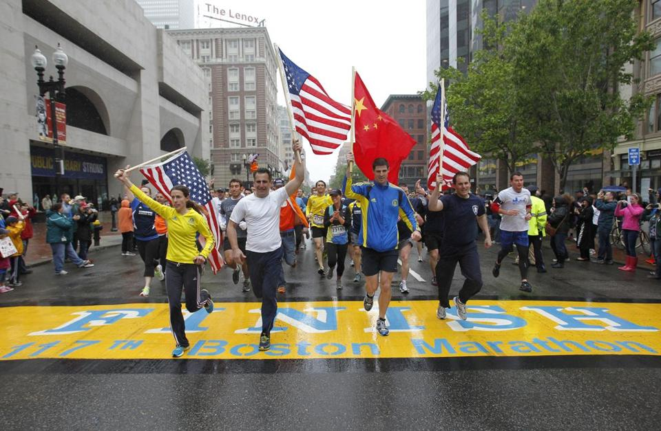 From left: Amanda Watters, Mike Ross, Kyle Shade and Andrew Truco carried flags as they crossed the Boston Marathon finish line on Boylston Street during the OneRun.