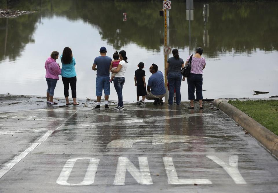A flooded intersection in San Antonio attracted more people than cars Sunday. Heavy rains and flooding are being blamed for at least three deaths in the region.